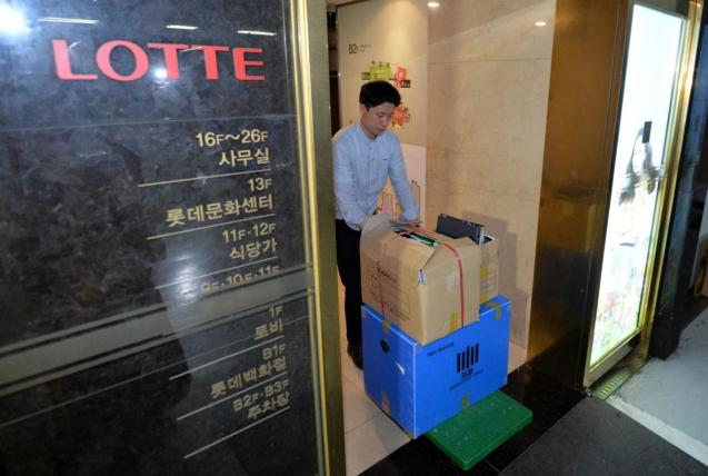 An investigator from the prosecution office carries boxes containing confiscated articles at Lotte Group's headquarters in Seoul